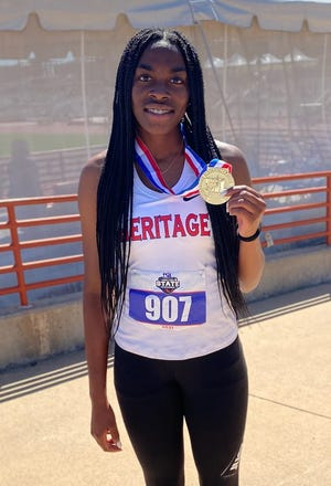 Midlothian Heritage junior Leah Anderson shows off one of two gold medals she earned at the University Interscholastic League Class 4A state championship meet on Thursday. Anderson won the triple jump and 100-meter hurdles, and added a silver medal in the 300-meter hurdles.