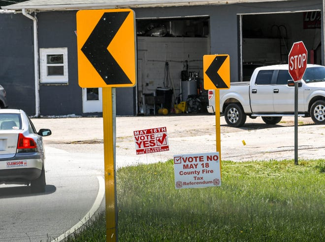 Cars drive along Whitehall Road in Anderson County, where signs asking people to vote for and against a county fire tax referendum.