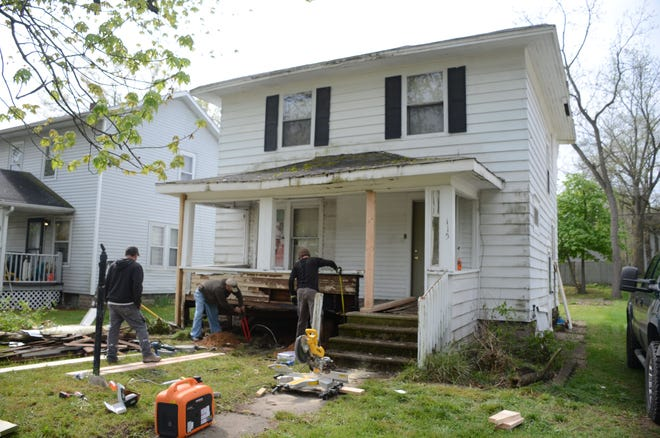 Workers were at 115 Bowen Ave. Friday repairing damage to the front porch after a fire Thursday.  (Trace Christenson/The Enquirer)