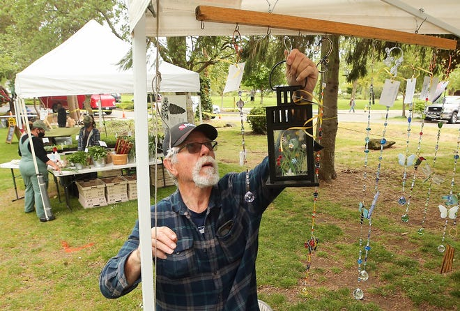 Randy Baas, of Gig Harbor, hangs a lantern with decorative glasswork by his wife, Diane, along the edge of her Diane's Dezines booth, for the opening day of the Bremerton Community Farmers Market at Evergreen Rotary Park in Bremerton on Thursday.