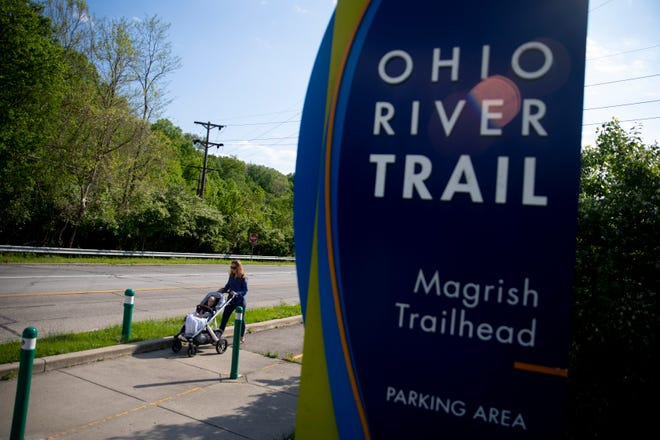 Bridget Henson pushes her son, John, 1, while walking on the Ohio River Trail next to Salem Road near a new link on the trail from Salem Road to Sutton Road on Friday, May 1, 2021.The completion of this link means pedestrians can bike 22 miles from Smale Riverfront Park to New Richmond on a trail or bike lane.