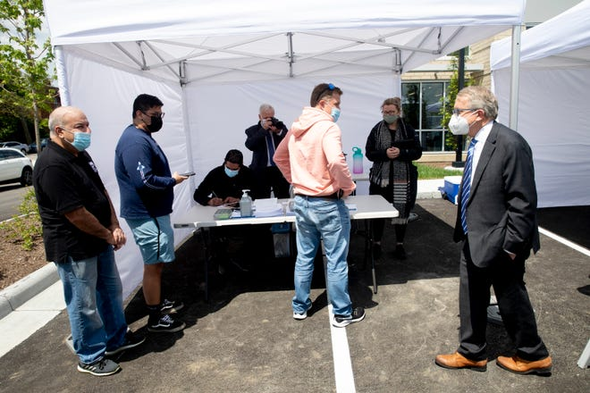Governor Mike DeWine, right, speaks to patients getting vaccinated during his visit to the Hamilton County mobile COVID-19 vaccination site at the Price Hill Library in East Price Hill on Friday, May 7, 2021.