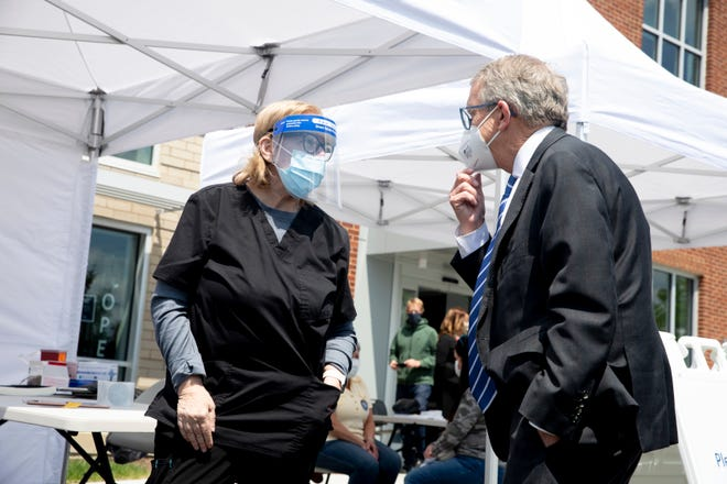 Registered nurse Carolyn Fitzpatrick speaks to Ohio Gov. Mike DeWine during his visit to the Hamilton County mobile COVID-19 vaccination site at the Price Hill Library in the Cincinnati neighborhood of East Price Hill on Friday, May 7, 2021.