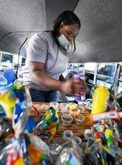 Paint'd Party Services owner and lead instructor LaShay Heard works on preparing painting kits on in her painting party bus.