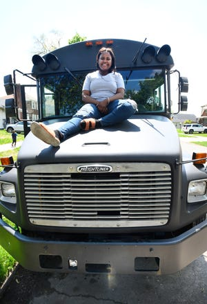 Paint'd Party Services owner and lead instructor LaShay Heard sits a top of her painting party bus in Detroit.