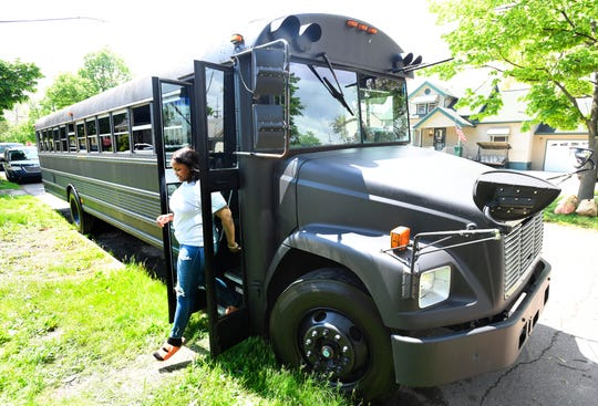Paint'd Party Services owner and lead instructor LaShay Heard and her painting party bus in Detroit.