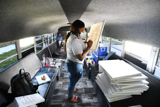 Paint'd Party Services owner and lead instructor LaShay Heard works on preparing canvases for painting in her painting party bus in Detroit, Michigan on May 7, 2021.