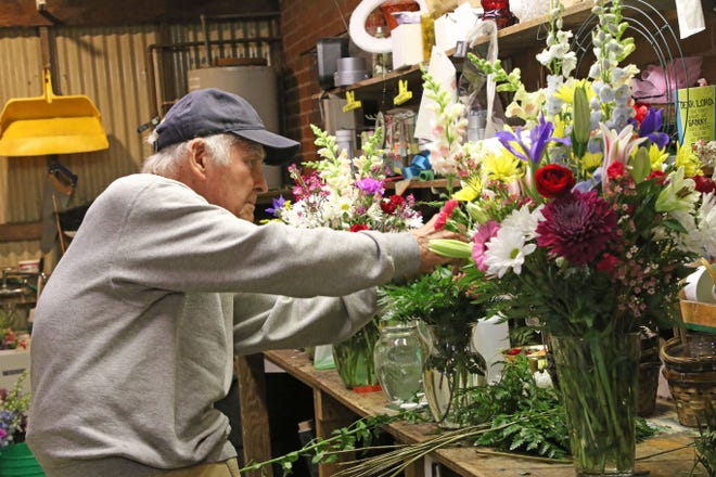 Ed Urban, co-owner of Otto and Urban Flowers & Greenhouse, prepares an arrangement at his shop in Fremont.