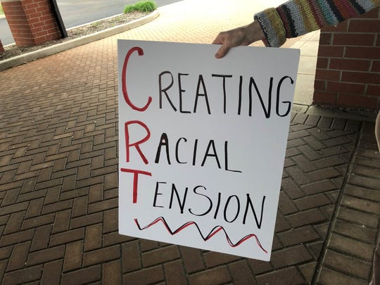 A protester holds a sign outside a building as the Noblesville school board meets inside on Tuesday, May 4, 2021. The protesters, who wouldn't provide their names, said they didn't want the schools to teach critical race theory, a concept that examines systemic racism as a part of American life. The district said it doesn't teach critical race theory.