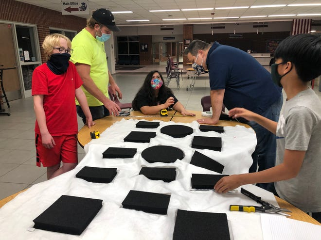 Team KRASH mentors and Highlander Way Middle School students cut a piece of foam for their KRASH Engineered Boxing Bag (KEBB) for patients with Parkinson's disease to stay mentally and physically fit.