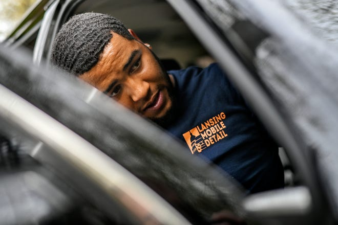 Martell Davis works on cleaning the inside of a customers vehicle at the customer's home on Thursday, May 6, 2021, in south Lansing. Davis, 18, started Lansing Mobile Detail in October with his brother, Undra Brown, and a friend, Faraji Loggins.