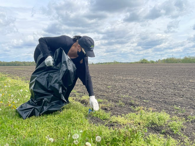 Angela Carbetta, director of Marion County Recycling and Littering, picks up trash alongside the farmland near River Valley High School.