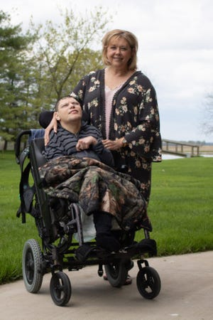 Jill Cowell, 57, of Marion, stands next to her son, Cody Cowell. The 29-year-old has cerebral palsy, which has affected his physical and mental abilities.