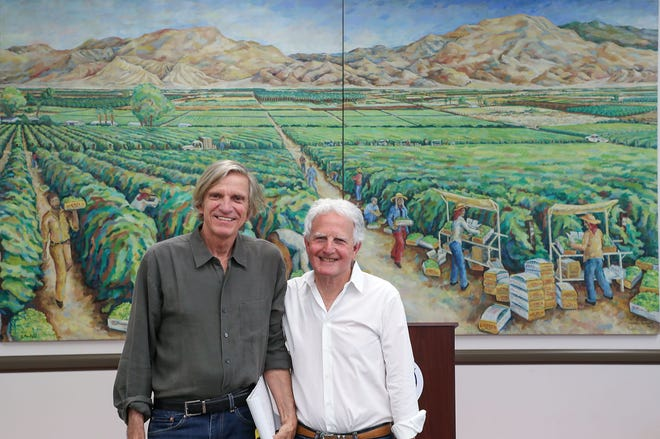 Artist Laurence Neufeld, left, and Billy Steinberg celebrate Neufeld's painting being gifted to the Coachella Library on Friday. The painting was commisioned by Steinberg's family in the 1970s when they were agricultural growers in the Coachella Valley.