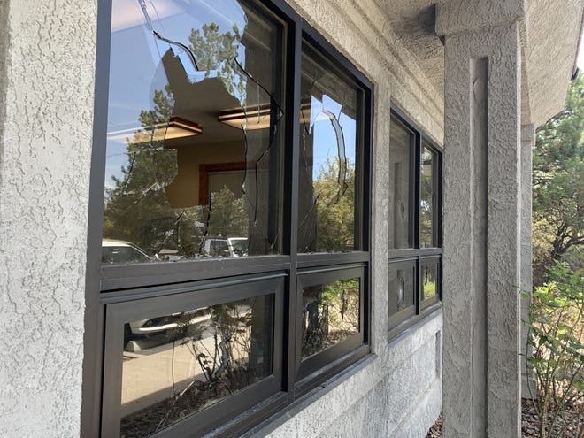 """The smashed window at HomeGate realty where bricks were thrown through on the night of May 5 with messages written and addressed by the """"Rent Is Too Damn High Party""""."""