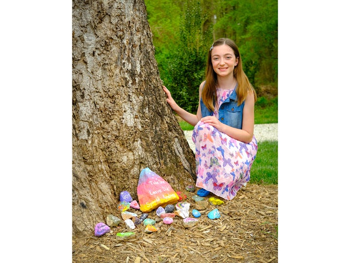 Madelyn Bubb with some of the kindness rocks she painted and placed in a neighborhood park.