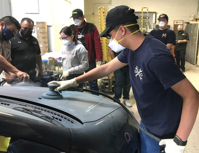 High school students and instructors in the youth automotive program DRAGG fix up a donated Toyota Matrix they'll be giving to a family in need in Oxnard on Saturday, May 8, 2021.