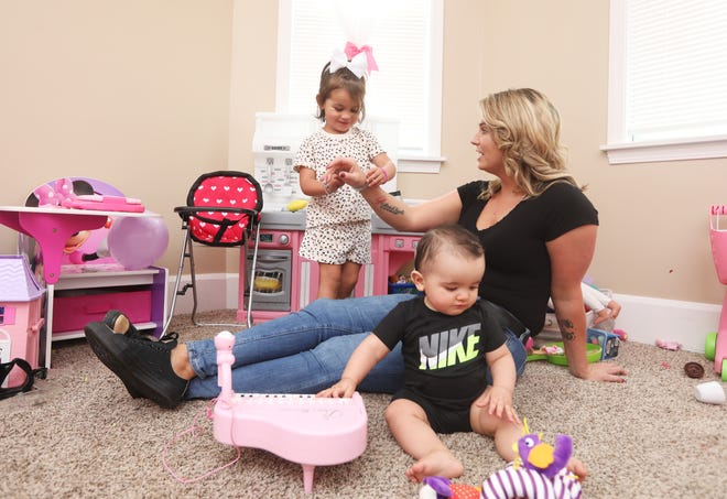 Karee Stemm plays with her children, Aleesiah, 3, and Koa, 7 months, in her Philo home. Karee grew up in fosters homes until she was adopted at the age of 14. Today she works with foster children and was recently awarded the Easter Ohio Everyday Hero award from the Ohio Children's Trust Fund.