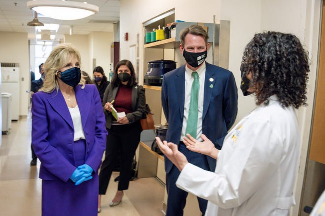 National Cancer Institute Director Dr. Ned Sharpless (at right) and First Lady Jill Biden receive a briefing from a research staff member during the First Lady's visit to the Massey Cancer Center in Richmond, VA on February 24, 2021.