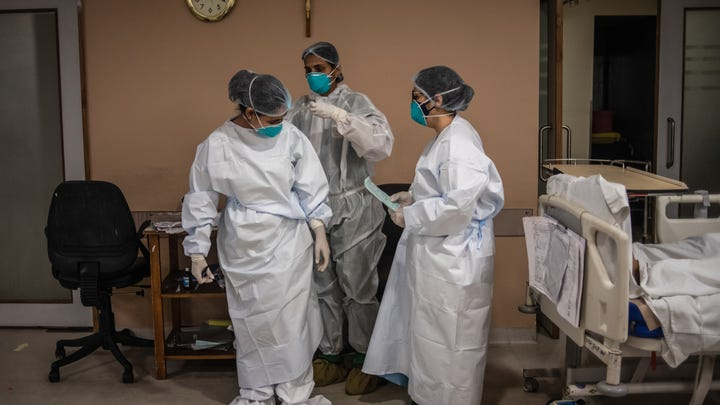 Medical staff help each other put on PPE equipment before attending to Covid-positive patients in the ICU ward at the Holy Family hospital on May 06, 2021 in New Delhi, India.