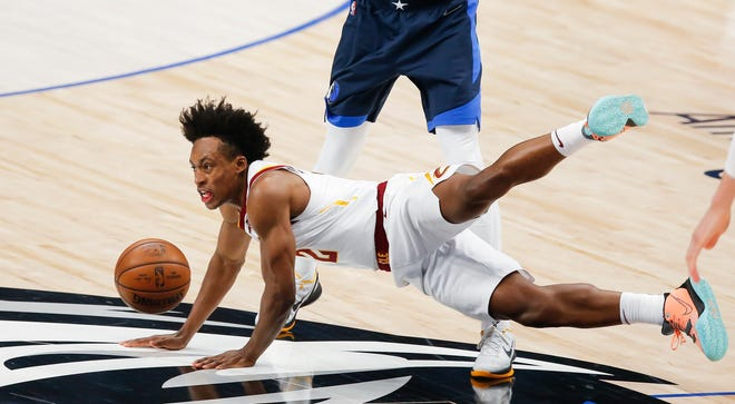 Cavaliers guard Collin Sexton (2) falls to the court after being  fouled by Dallas Mavericks forward Dorian Finney-Smith during the first half of the Mavericks' 110-90 win Friday night. [Brandon Wade/Associated Press]