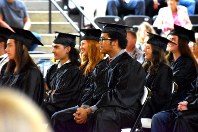 Wilson High School graduates smile as a video presentation of classmates is shown during a commencement ceremony Friday, May 7, 2021.