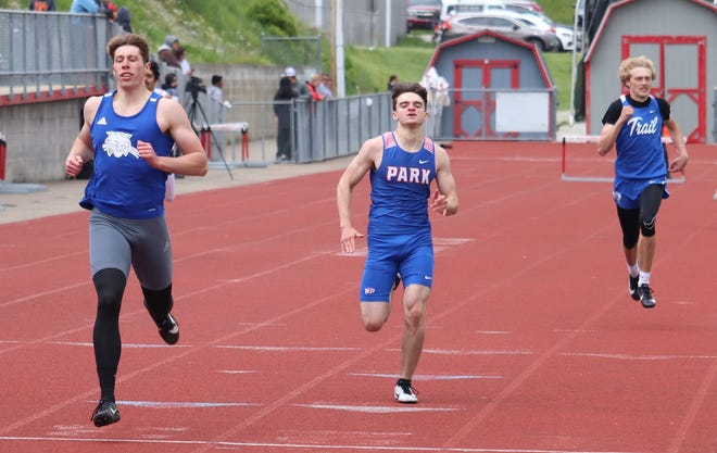 Cambridge senior Dominic Cork, far left, crosses the finish line for the victory in the boys 400 meter with a time of 52.41 on Saturday at the OVAC Track Championships at St. Clairsville High School. Buckeye Trail's  Donovan Geiger, far right, came on to take runner-up.