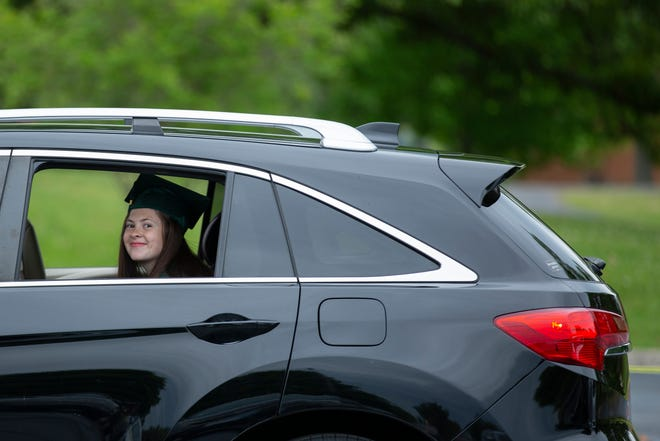 Isabell Twig rides in the back of an SUV during a drive-thru graduation ceremony at Columbia State Community College in Columbia, Tenn., on Saturday, May 8, 2021.
