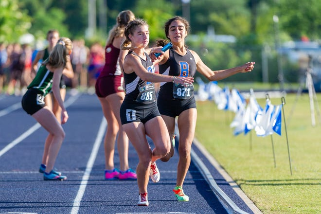 Bolles' Layne Rivera (885) gets the baton from Leila Bata (871) in the girls 4x800 relay.