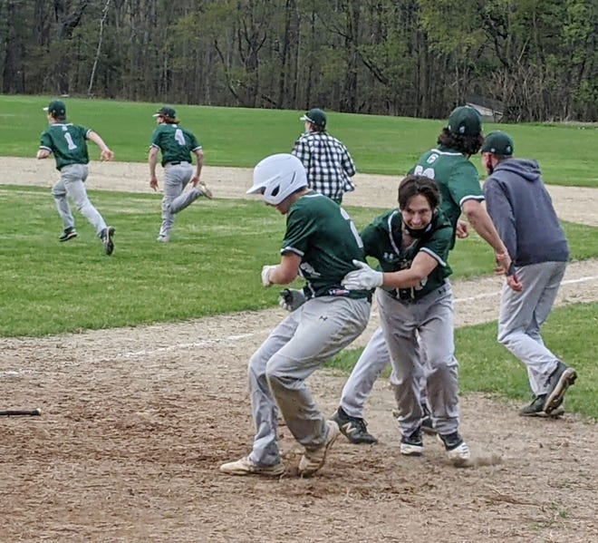 As their teammates rush the field to chase down Watson Mexico, Oakmont's Bill Wirtinen, right, celebrates the Spartans' 10-9, nine-inning win over Clinton with Colby Gouldrup, who scored the game-winning run, Friday, in Ashburnham.