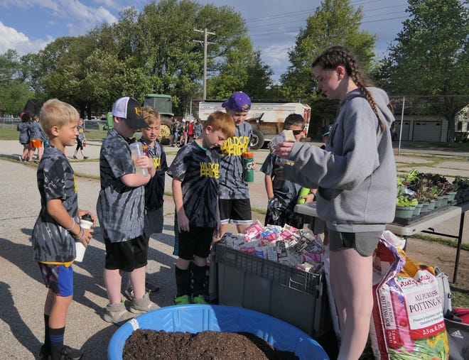 Allyson Bosley, a ninth grader, shows Haven Primary School students how to plant lettuce seeds.