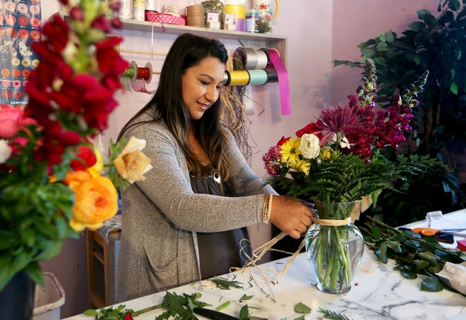 Taisha Epp creates a bouquet of flowers for a customer at her shop, LuvBlossoms, at 109 East Third Ave in Buhler.