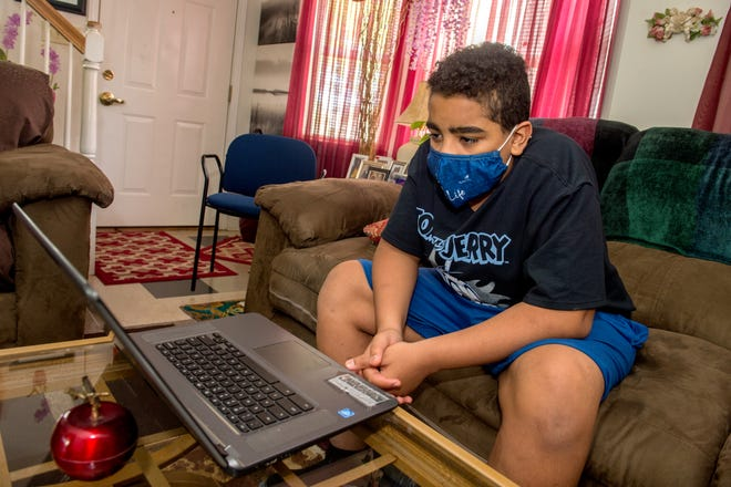 Bryson Marshall, 13, watches the virtual awards ceremony for students in the SkillsUSA program at his great-grandmother's home in the RiverWest complex in Peoria.