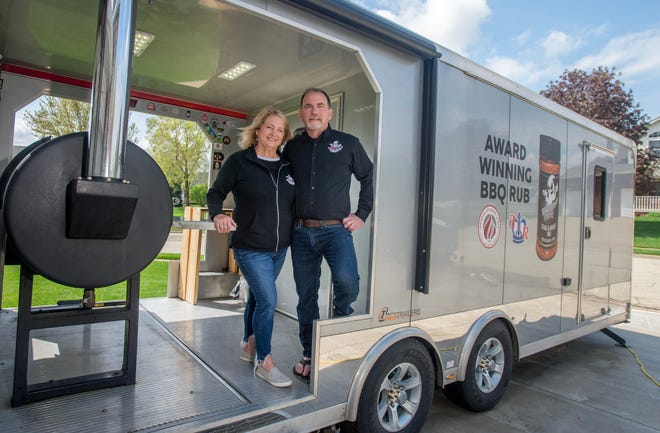Paul and Sarah Buob of Chillicothe pose in the rolling kitchen they haul to barbecue competitions across the country. The Buobs have created their own award-winning barbecue sauce and rub under the SmokinGhost BBQ brand.