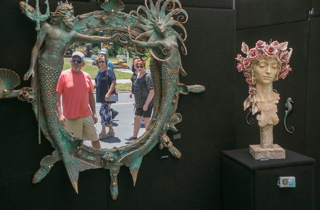 Festival attendees are reflected in the nautical themed sculpture mirror by artist Ruben D. Medina of Cape Coral, as they stroll along Lake Morton Drive during the annual Mayfaire by-the Lake in Lakeland Saturday.