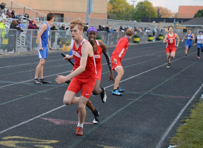 Ayden Roupe gets the baton from New Boston Huron teammate Antonio Talley in the distance medley relay at the Flat Rock Ram Relays Friday. Huron won the event and went on to capture the boys team title.