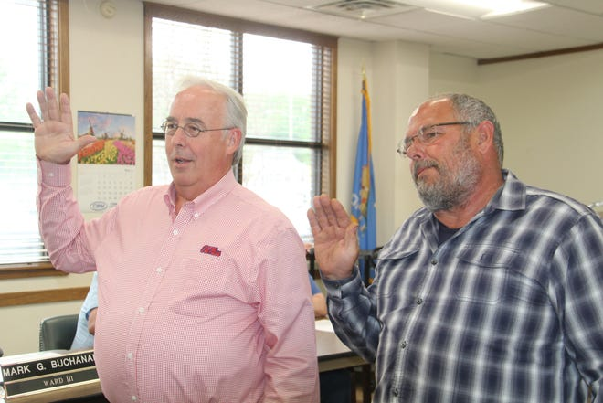 Mark Buchanan, left, and Rodger Milleson, right, take the oath of office to begin new three-year terms on the Pawhuska City Council. Buchanan, the incumbent Ward 3 councilor, won re-election. Milleson, who previously served as at-large councilor, has now been elected Ward 4 councilor.
