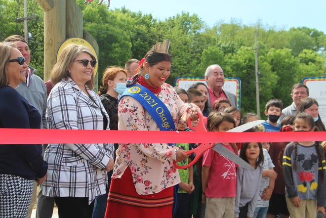 """Gianna """"Gigi"""" Sieke, Osage Nation princess, cuts the ribbon to officially open the new Wahzhazhe Heritage Trails in Pawhuska. The opening ceremony took place the morning of May 5 at the trail head, located next to the municipal veterans memorial."""
