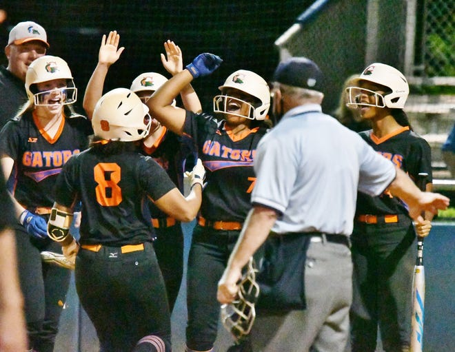 Palm Beach Gardens players gather around home plate to celebrate Kairi Rodriguez's three-run home run in the bottom of the sixth inning. The big hit all but sealed the 8-3 victory in what had been a back-and-forth regional quarterfinals game on Friday night.