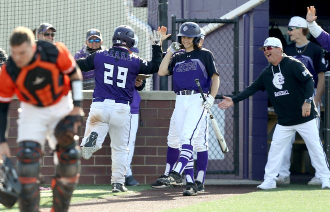 Jackson's Alex Snyder (29) heads back to the dugout after scoring in the first inning against Massillon.