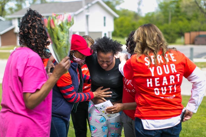 Trinetta Holmes, in red hat, and Tiffney Rhodes, second from right, give prayers of comfort to Partenia Thornton, center, Saturday, May 8, 2021, at Orton Keyes Court in Rockford after learning of the death of Thorton's mother. Volunteers were at the public housing complex Saturday to deliver Mother's Day gifts to residents.