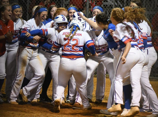 Southern Alamance's Nikki Vaughn is met at home plate by teammates after hitting a two-run homer in the seventh inning of Friday's playoff win against Topsail.