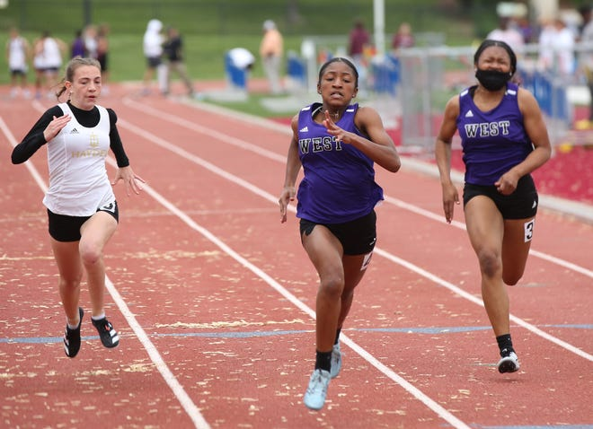 Topeka West freshman Victoria Reed (middle) powers her way to the win in the girls' 100-meter dash at Friday's Joe Schrag City Invitational at Hummer Sports Park. Reed won the 100, 400 and was on West's winning 400 relay.