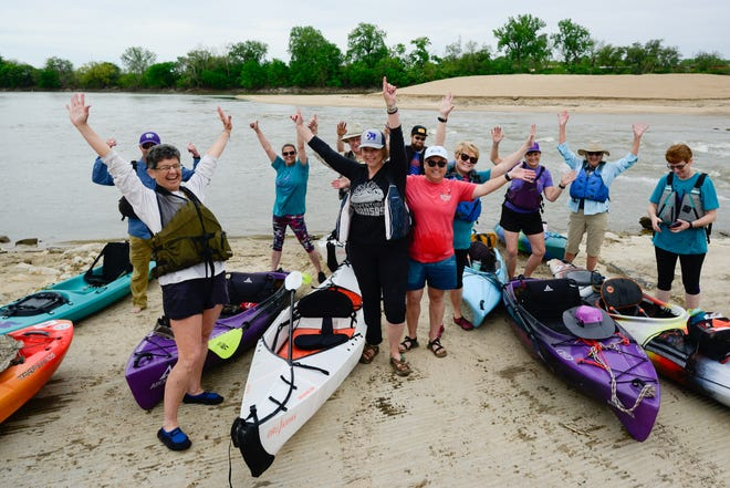 Kayakers who helped bring in the newly developed weir area off the Kansas River pose for a photo before a dedication ceremony Friday afternoon.