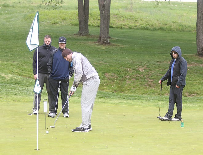 Ethan Edie, Erich Kertz, Matt Bender and Tyler Mack  putt on the 15th hole  at the Oak Shadows Golf Club's Re-Opening Outing Saturday.