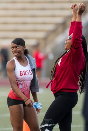 Bosse's Alexia Smith is surprised as her coach Jennifer Martin celebrates Smith setting a new 400-meter record with a time of 57.14 seconds on May 7 in the SIAC girls' track and field meet at Central Stadium.