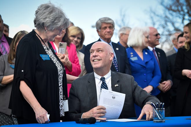 FILE - In this Monday, April 26, 2021, file photo, Republican Gov. Greg Gianforte smiles at Rep. Sharon Greef, R-Florence, during the signing of a bill in Helena, Mont. Gianforte signed three bills restricting abortion access in the state, celebrating it as a success after several attempts to pass similar measures in the previous year were vetoed by former Democratic governors. Gov. Gianforte signed another bill Friday, May 7, banning transgender athletes from participating in school and university sports according to the gender with which they identify, making Montana the latest of several Republican-controlled states to approve such measures this year. (Thom Bridge/Independent Record via AP, File)