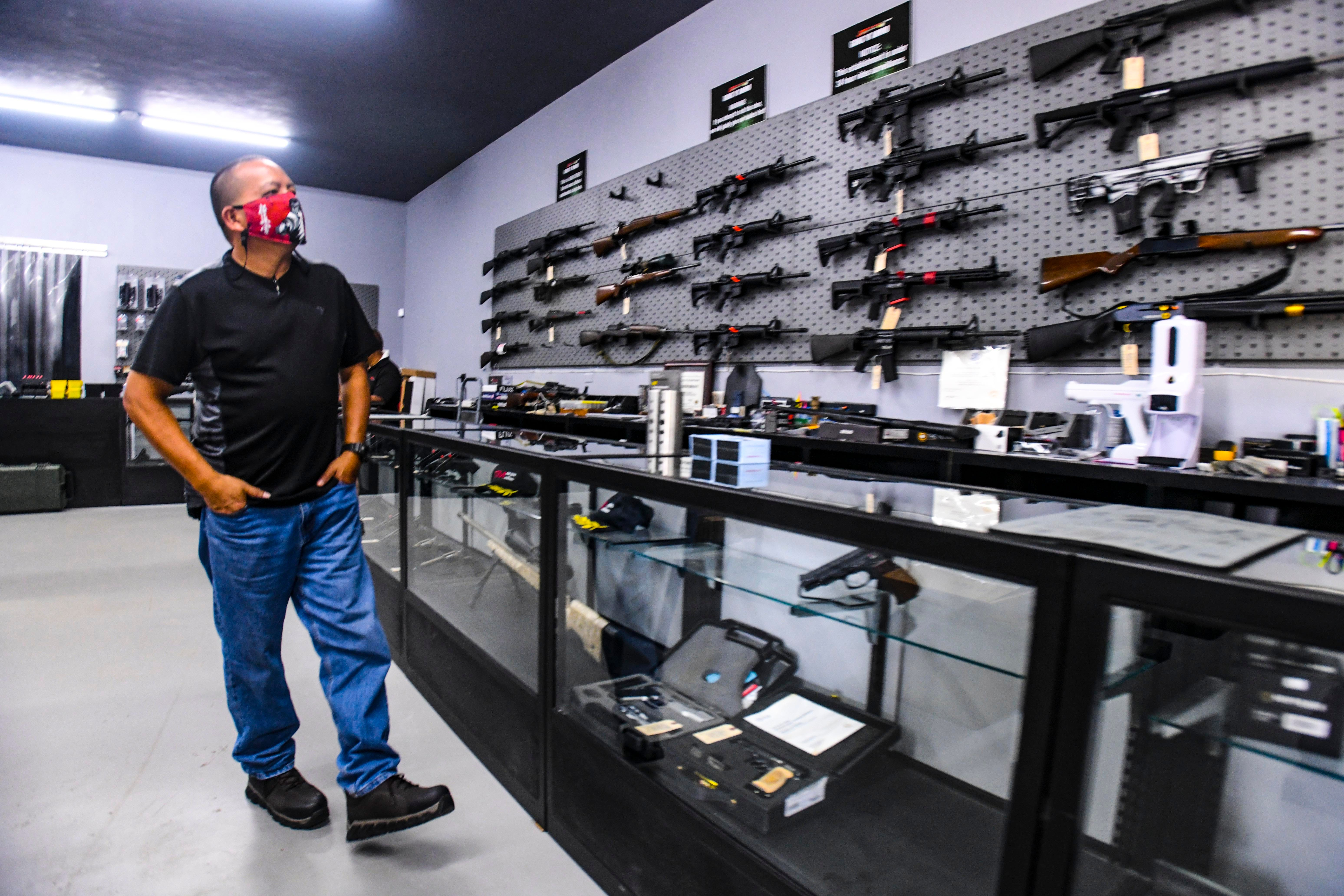 Piti resident Rich Perez looks over the collection of firearms displayed for sale at JTM Benchrest in Dededo May 8, 2021. Along with the gun shop, the business also operates the Sportsland Outdoor Shooting Range.
