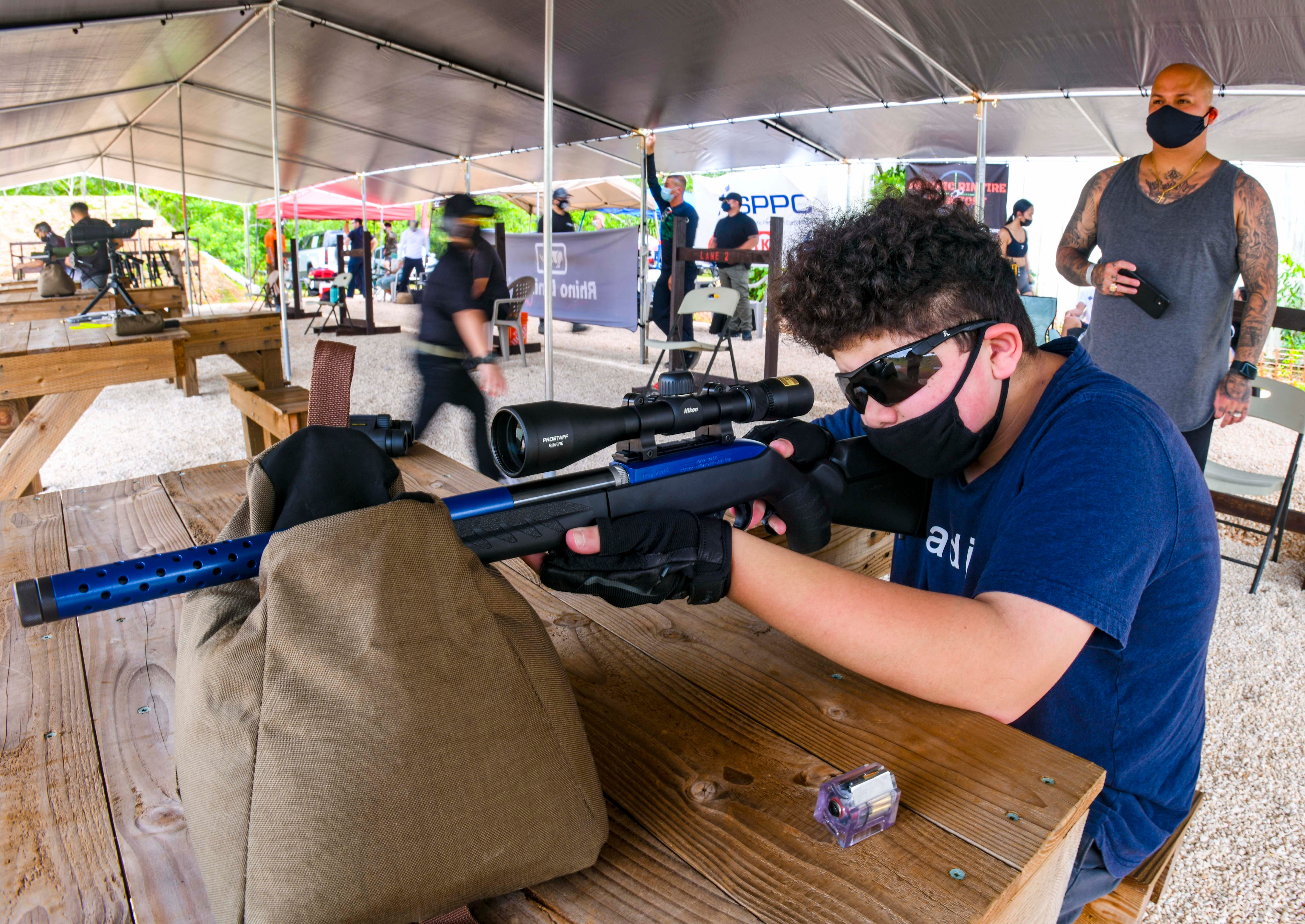 Andrew Martinez, 13, prepares to engage targets downrange as his father, Alberto Martinez, watches from behind during the Pacific Rimfire Shootout at the Sportsland Outdoor Shooting Range in Dededo on Saturday, May 8, 2021.