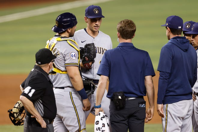 Brent Suter talks with a trainer and manager Craig Counsell before leaving the game Friday night due to an injury in the third inning against the Marlins.